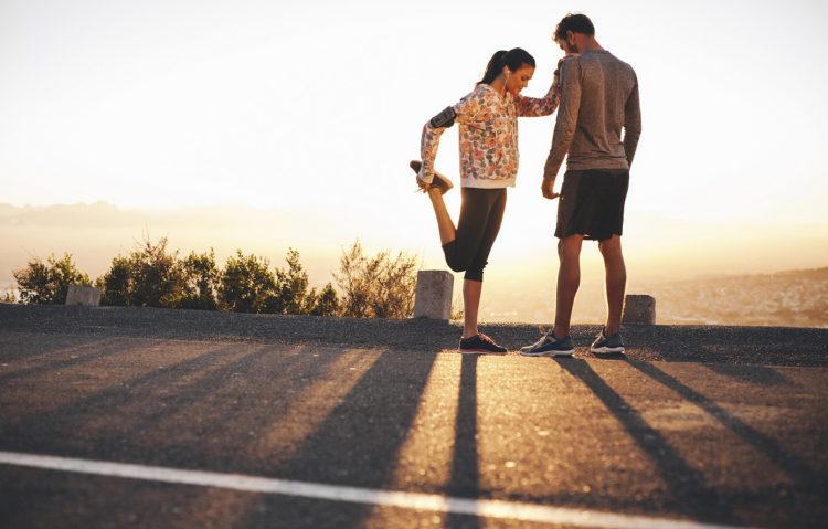 Outdoor shot of fit young joggers stretching before a run together in morning. Young man standing and woman stretching her legs at sunrise.