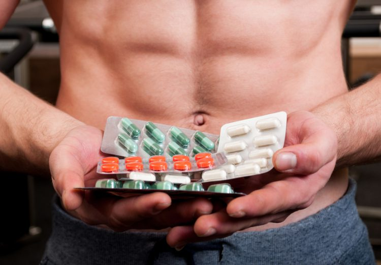 Muscle man holding bunch of blisters with colored vitamin pills