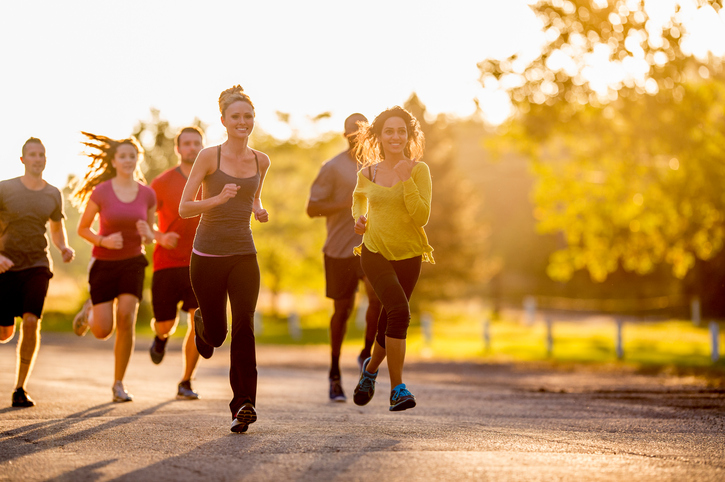 A multi-ethnic group of young adults are running outside at the park on a beautiful sunny evening around dusk.